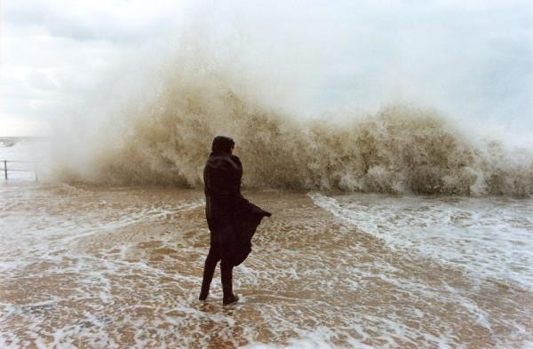 Persoon op zeedijk tijdens storm