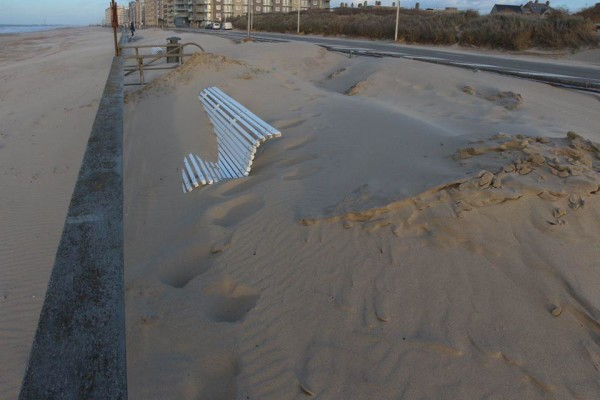 Zand op zeedijk na storm